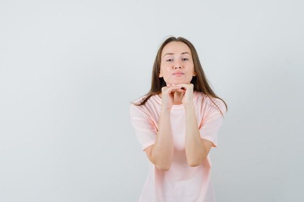 손에 턱을지지하고 좋은, 전면보기를 찾고 분홍색 티셔츠에 젊은 여성.