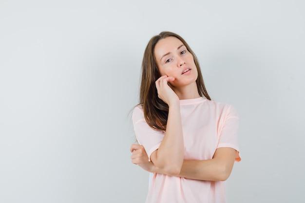 뺨에 그녀의 얼굴 피부를 만지고 매혹적인, 전면보기를 찾고 분홍색 티셔츠에 젊은 여성.