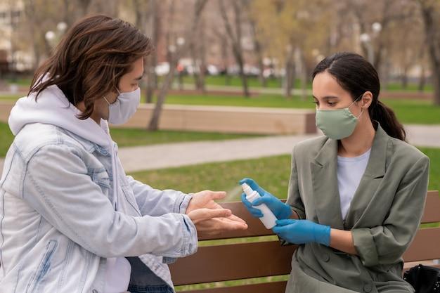 보호 장갑과 그녀의 남자 친구의 손에 소독제를 살포하는 마스크에 젊은 여성