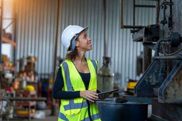 産業機械を検査し、工場でデジタルタブレットに必要なメモを取る保護制服を着た若い女性。