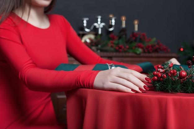 Молодая женщина в красном платье, крупным планом руки.