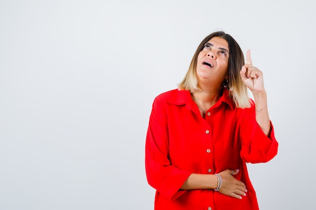 빨간색 특대형 셔츠를 입은 젊은 여성이 위를 가리키고 어리둥절한 표정을 짓고 있습니다.