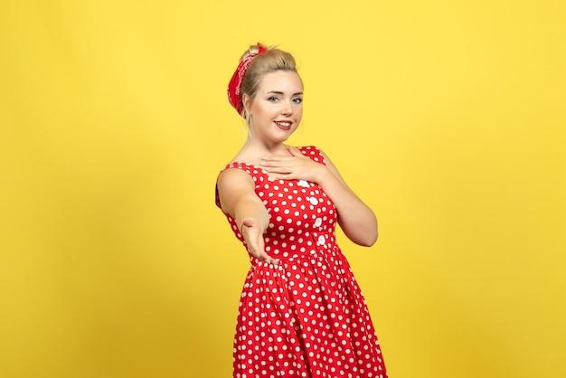 黄色の彼女の手で誰かに挨拶する赤い水玉模様のドレスの若い女性