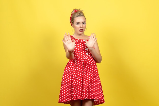 ちょうど黄色の上に立っている赤い水玉模様のドレスの若い女性