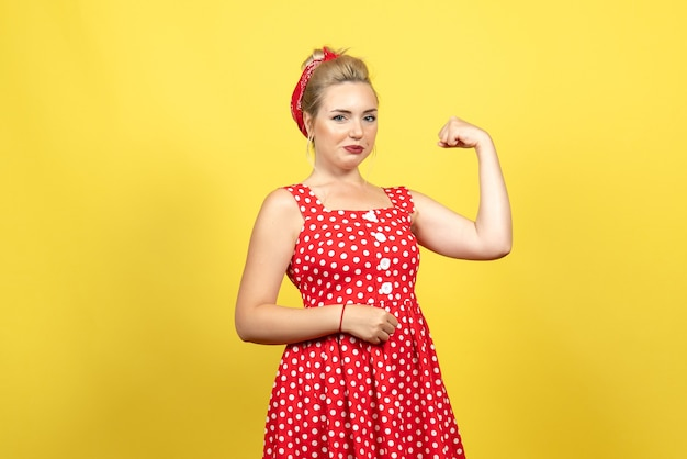Молодая женщина в красном платье в горошек позирует и сгибается на желтом