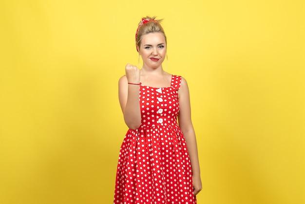 Молодая женщина в красном платье в горошек позирует на желтом