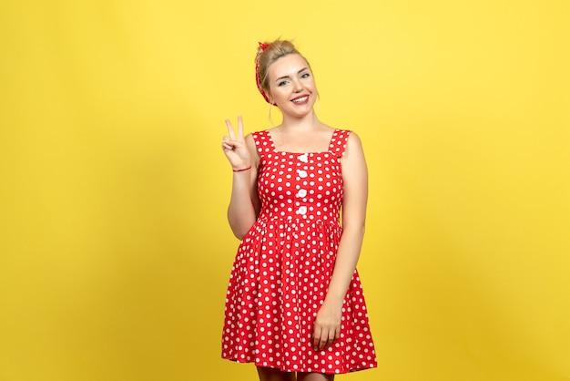 黄色の笑顔でポーズをとって赤い水玉模様のドレスの若い女性