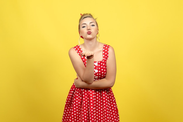黄色の空気のキスを送信する赤い水玉模様のドレスの若い女性