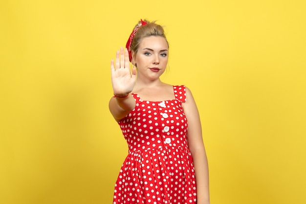 Молодая женщина в красном платье в горошек показывает знак остановки на желтом