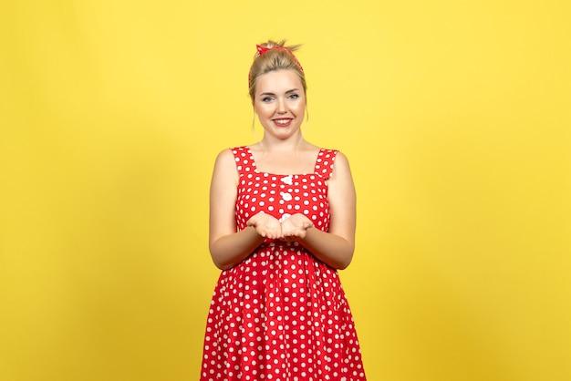 Молодая женщина в красном платье в горошек улыбается желтому