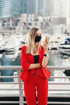 Молодая женщина в красном костюме в маске черного цвета стоит на улице и читает что-то на смартфоне
