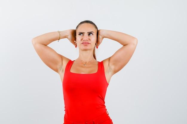 赤いタンクトップの若い女性、頭に手をつないで物思いにふけるパンツ、正面図。