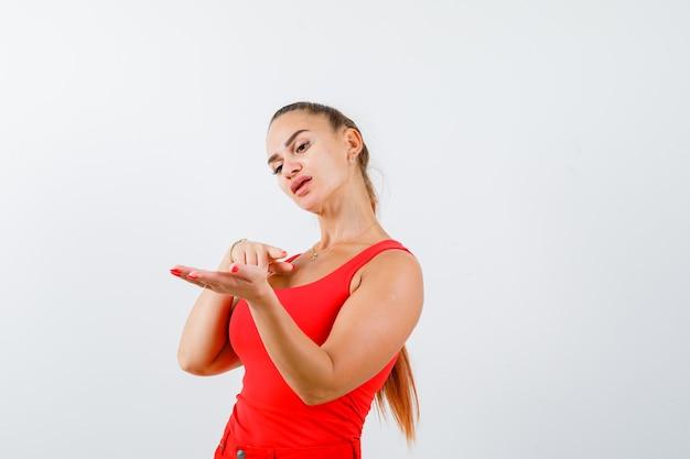 赤いタンクトップの若い女性、何かを見せているふりをして自信を持って見えるパンツ、正面図。