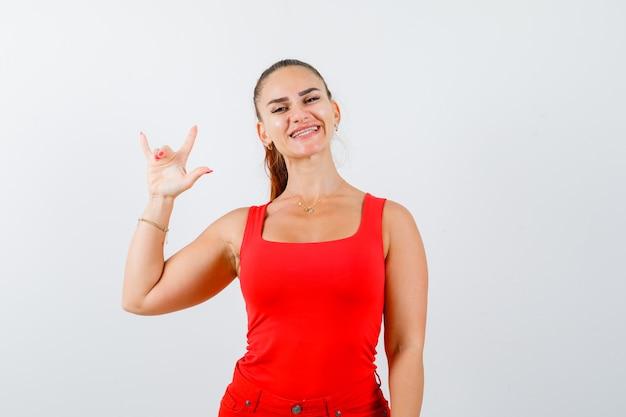 赤いタンクトップの若い女性、ズボンを見せていますか?あなたのジェスチャーを愛し、かわいく見える、正面図。
