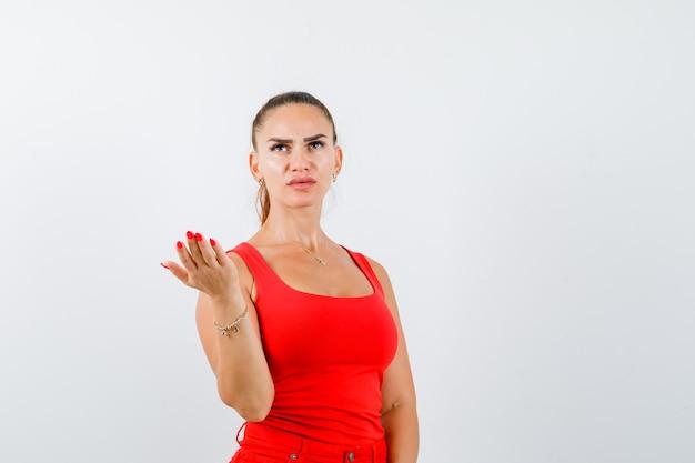 赤いタンクトップの若い女性、ジェスチャーを質問し、真剣に見える、正面図で手を伸ばしてパンツ。