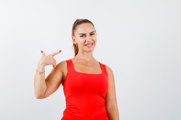 右側を指して幸せそうに見える赤いタンクトップの若い女性、正面図。