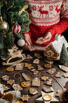 クリスマスジンジャーブレッドクッキーを保持しているトナカイのセーターの若い女性