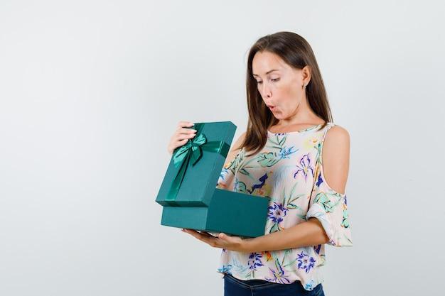 셔츠에 젊은 여성, 열린 된 선물 상자를 찾고 청바지를 찾고 놀라게, 전면보기.