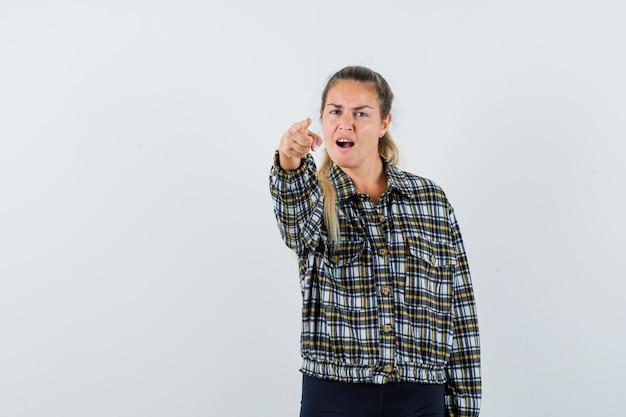 Молодая женщина в рубашке, шортах, указывая на камеру и нервно глядя, вид спереди. Бесплатные Фотографии