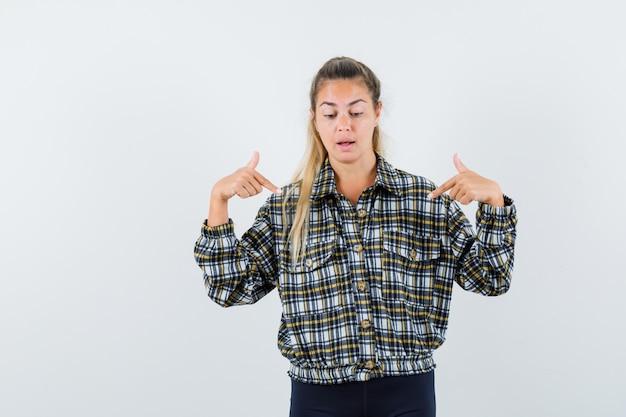 셔츠에 젊은 여성, 아래쪽을 가리키고 초점을 맞춘 찾고 반바지, 전면보기.