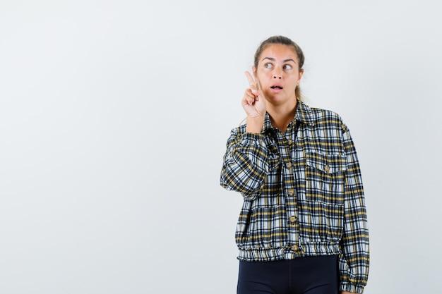 셔츠에 젊은 여성, 손가락을 가리키는 반바지, 잠겨있는, 전면보기를 찾고.