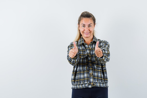 シャツを着た若い女性、両手の親指を上に向けて自信を持って見えるショートパンツ、正面図。