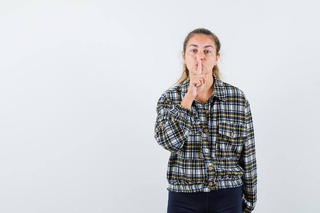 シャツを着た若い女性、沈黙のジェスチャーを示し、賢明に見えるショーツ、正面図。