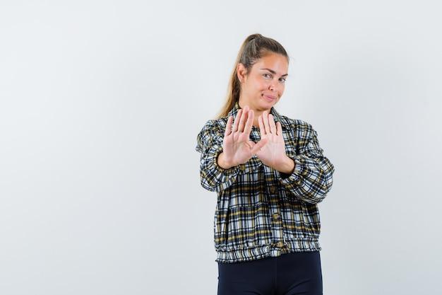 シャツを着た若い女性、停止ジェスチャーを示し、自信を持って見えるショーツ、正面図。