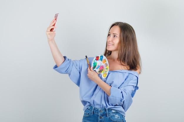 Молодая женщина в рубашке, шортах делает селфи с инструментами для рисования и выглядит весело.