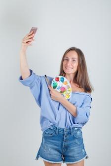 Молодая женщина в рубашке, шортах, делающая селфи с инструментами для рисования