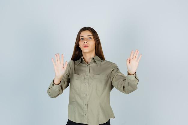 停止ジェスチャーを示し、怖がって見えるシャツの若い女性、正面図。