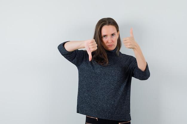 上下に親指を示し、躊躇しているシャツを着た若い女性