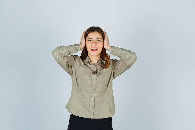 シャツを着た若い女性、手で頭を握りしめ、幸せそうに見えるスカート、正面図。