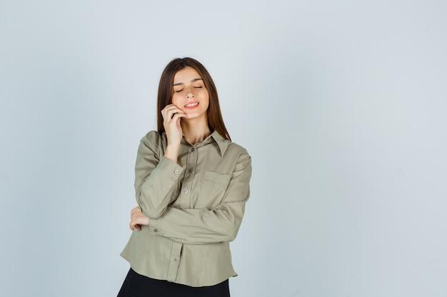 셔츠를 입은 젊은 여성, 치마는 손가락으로 뺨의 얼굴 피부를 검사하고 평화로운 앞모습을 보고 있습니다.