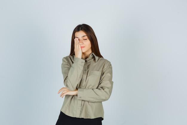 Молодая женщина в рубашке, юбке держит руку на глазах и выглядит усталой