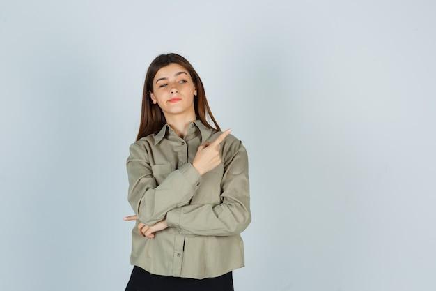 셔츠를 입은 젊은 여성, 오른쪽 위 모서리를 가리키는 치마, 구부러진 입술, 자신감 있는 앞모습.