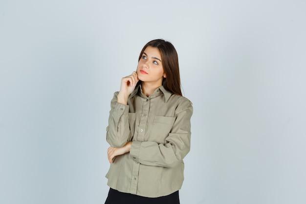 셔츠에 젊은 여성, 손에 턱을지지하고 사려 깊은 찾고 치마