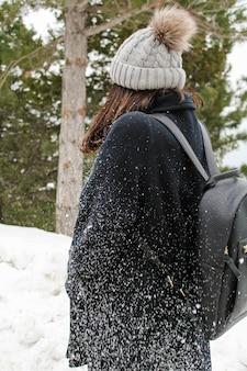 雪だるま後の雪の中の若い女性