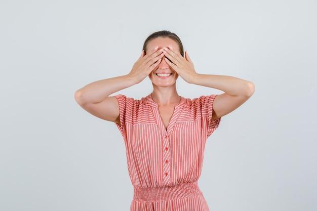 手で目を覆い、興奮して見える縞模様のドレスを着た若い女性、正面図。