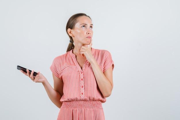 Молодая женщина в полосатом платье держит мобильный телефон, глядя вверх и задумчиво, вид спереди.