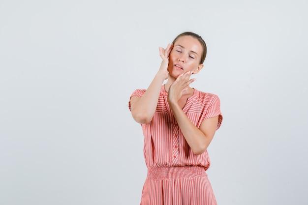 こめかみを丁寧にこすり、リラックスして見える縞模様のドレスを着た若い女性、正面図。
