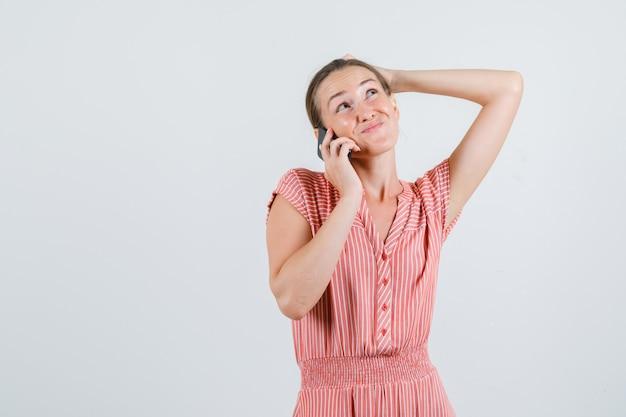 Молодая женщина в полосатом платье разговаривает по мобильному телефону и нерешительно смотрит, вид спереди.
