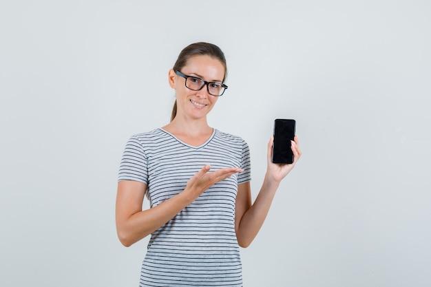 Молодая женщина в полосатой футболке, очках показывает мобильный телефон и рад, вид спереди.