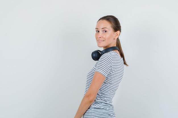 Молодая женщина в полосатой футболке, наушниках и веселый взгляд.