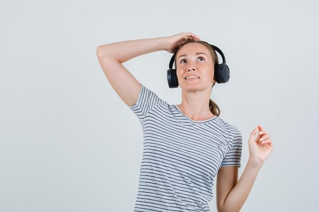 ヘッドフォンで注意深く聞いている縞模様のtシャツの若い女性、正面図。