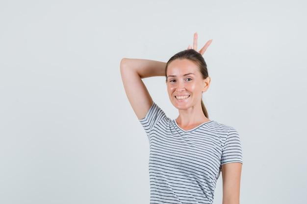 頭の後ろにvサインを示し、面白い、正面図を示すストライプのtシャツの若い女性。