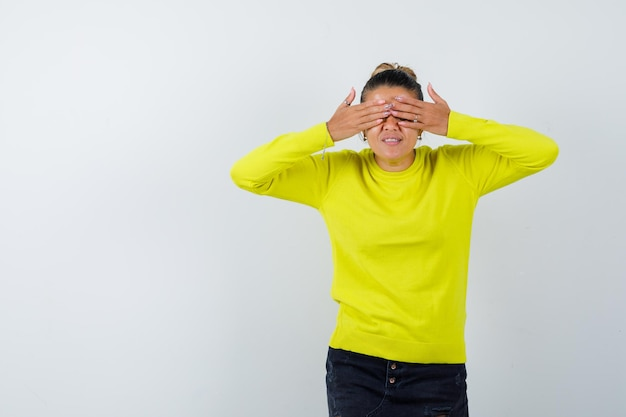 Молодая женщина в свитере, джинсовой юбке закрывает глаза руками и выглядит мило
