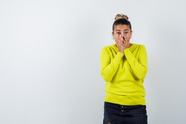 Молодая женщина в свитере, джинсовая юбка закрывает лицо рукой и выглядит изумленно