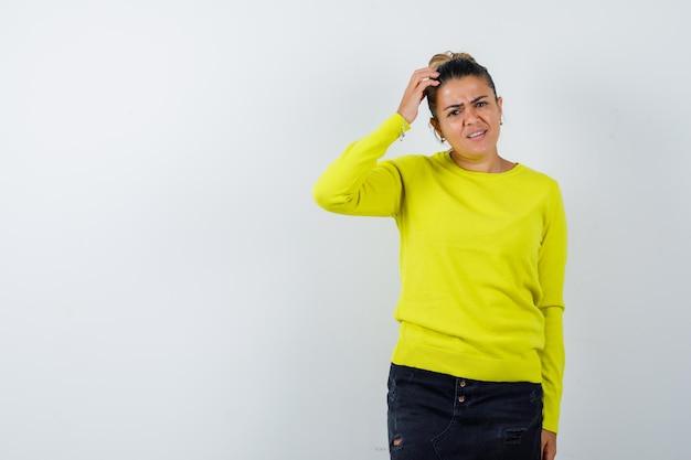 セーター、デニムスカートの頭を引っ掻いて物思いにふける若い女性
