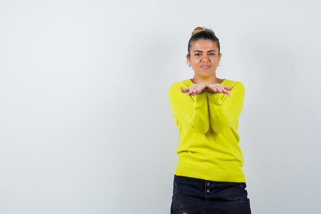 セーターを着た若い女性、カップ状の手を伸ばして至福に見えるデニムスカート